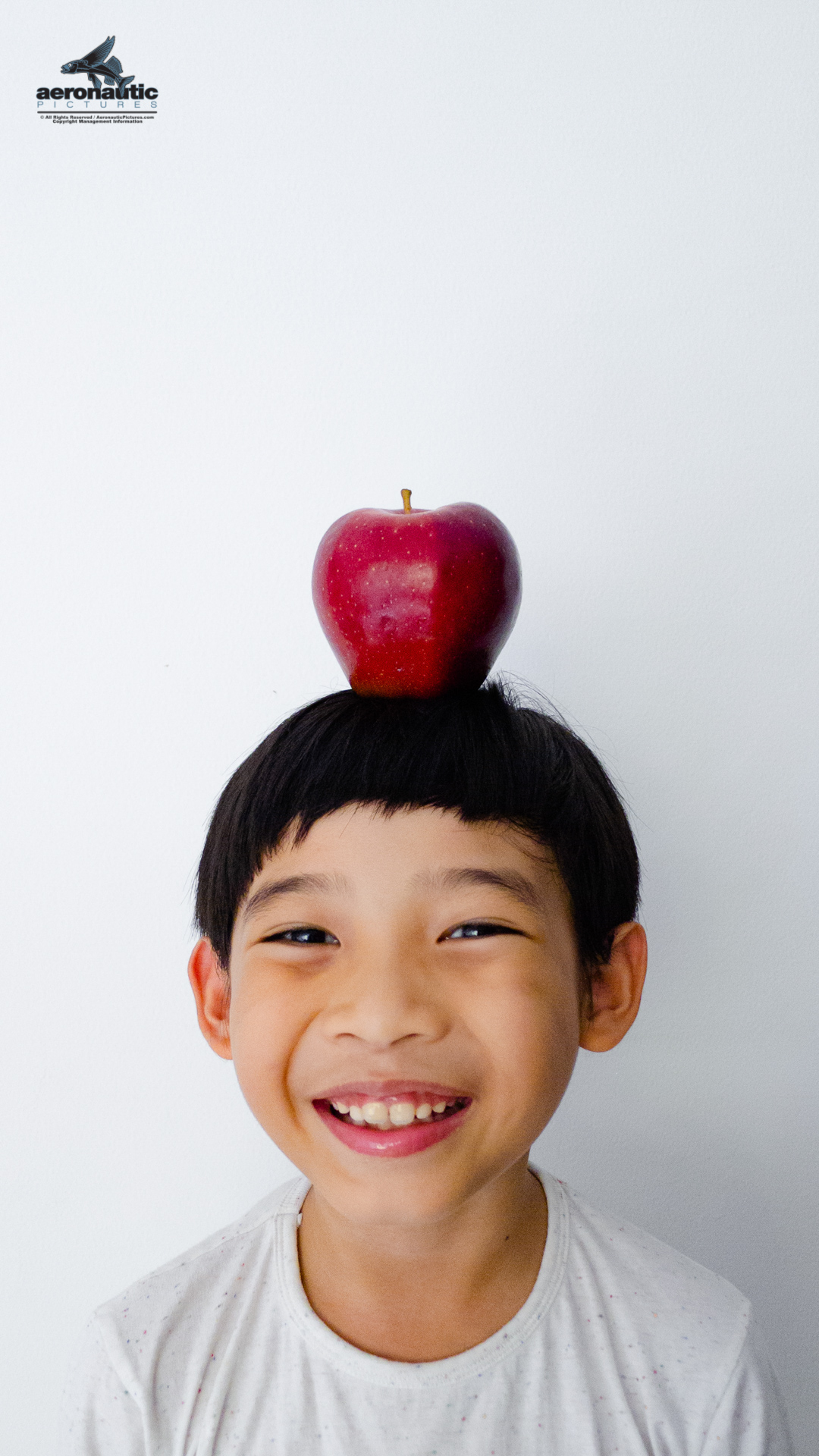 Happy Boy Child Smiling with Apple on His Head