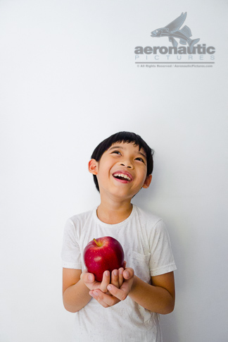 Food Stock Photo - A Happy Kid Laughing Out Loud While Holding an Apple Download