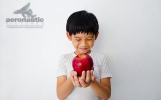 Food Stock Photo - A Happy Kid Smiling and Holding an Apple