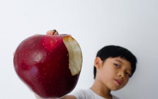 Food Stock Photos - A Kid Showing off a Bitten Apple Download Bite Out Of Apple Now!