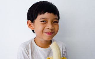 Food Stock Photo - A Happy Kid Eating a Banana Download Royalty Free