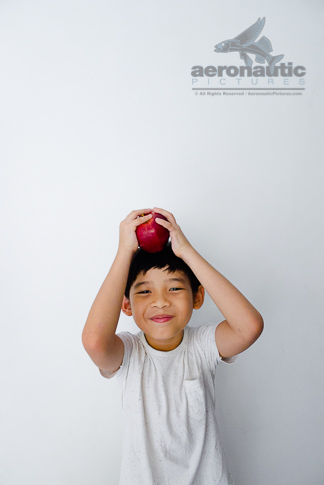 Food Stock Photo - A Happy Kid Holding an Apple Over His Head Download