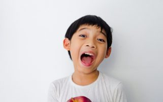 Food Stock Photos - A Happy Kid Holding an Apple Download Royalty Free Cheap