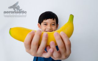 Food Stock Photo - A Happy Kid Holding a Banana Download Royalty Free