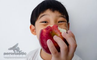 Food Stock Photo - A Happy Kid Holding a Half-eaten Apple - Download Royalty Free