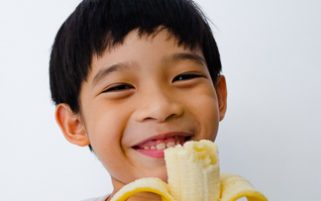 Food Stock Photo - A Happy Kid Holding a Half-eaten Banana Download