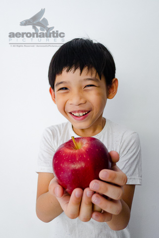 Food Stock Photo - A Happy Kid Laughing While Holding an Apple Download Now!