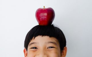 Food Stock Photo - A Happy Kid Smiling Widely with an Apple on His Head Royalty Free Download