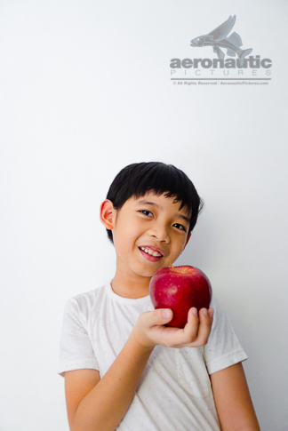 Food Stock Photo - A Healthy Kid Smiling Happily While Holding an Apple Download Royalty Free!