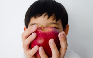 Food Stock Photo - A Kid Covering His Face Playfully with an Apple Download
