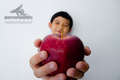 Food Stock Photo - A Kid Giving You a Red Delicious Apple Download Cheap