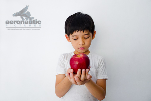 Food Stock Photo - A Kid Holding an Apple in Front of Him - Download Royalty Free