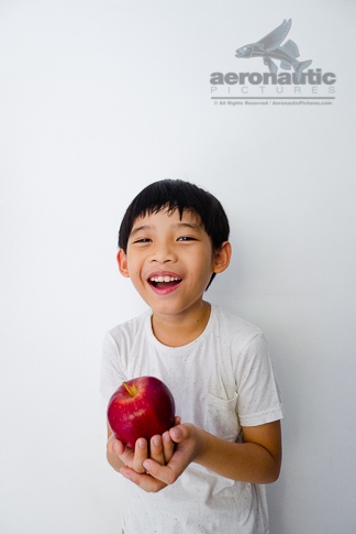 Food Stock Photo - A Kid Holding an Apple, Laughing Happily - Download Royalty Free