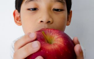 Food Stock Photo - A Kid Looking Closely at an Apple Download Royalty Free