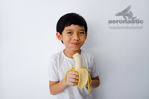 Food Stock Photo - A Kid Looking Happy While Eating a Banana Download