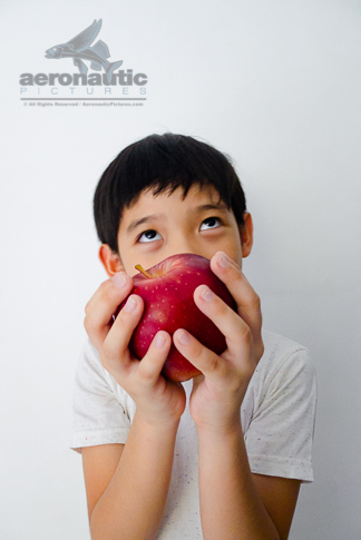Food Stock Photo - A Kid Thinking and Holding an Apple Download Royalty Free